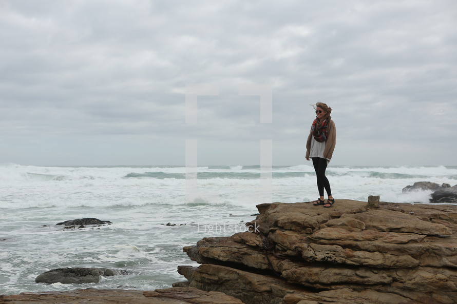 Woman standing on large rocks on ocean