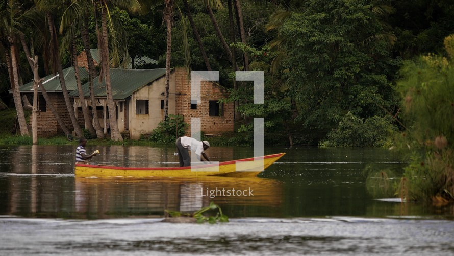 homes under palm trees along a river Uganda