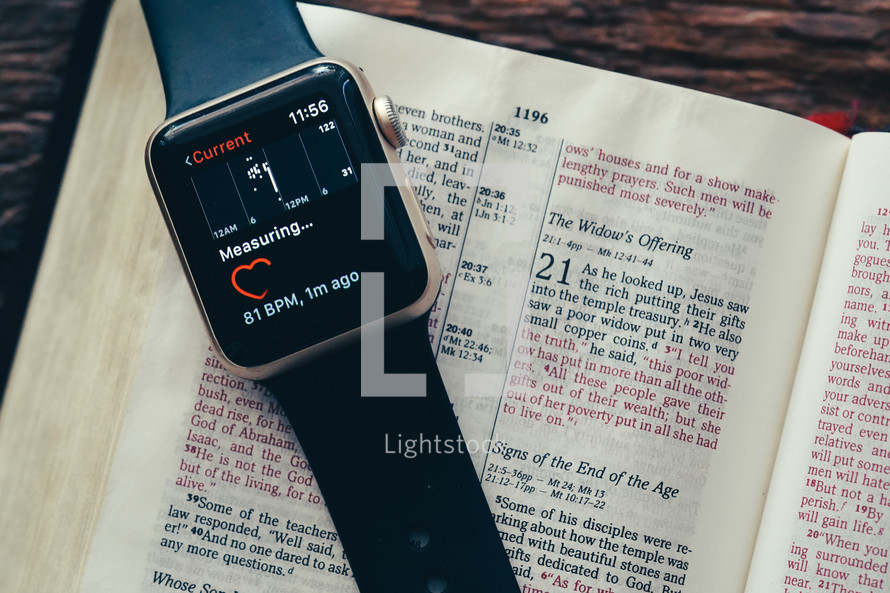 smartwatch on the pages of a Bible