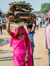 woman and boy carrying items on their heads in India