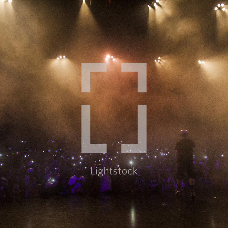 Man performing on stage and audience with lighters raised.