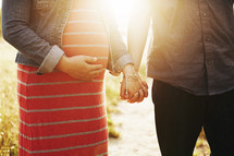 pregnant woman and man holding hands
