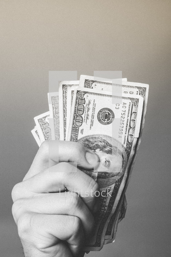 Hand grasping stack of paper money.