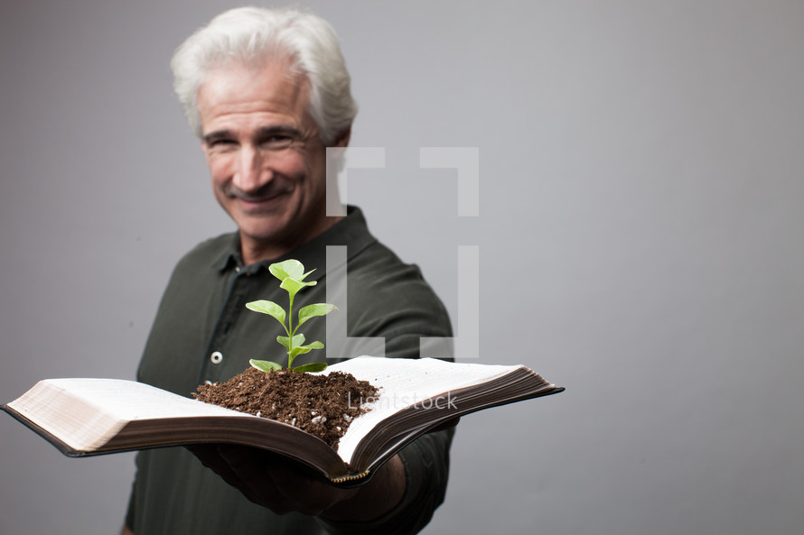 man holding a Bible with a plant growing from its pages