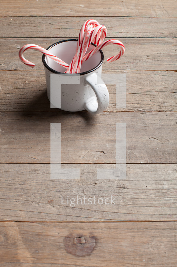 candy canes in a mug on a wood floor