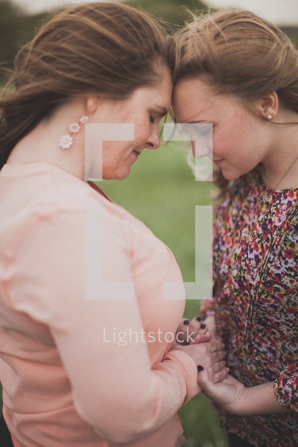 mother and daughter standing forehead to forehead