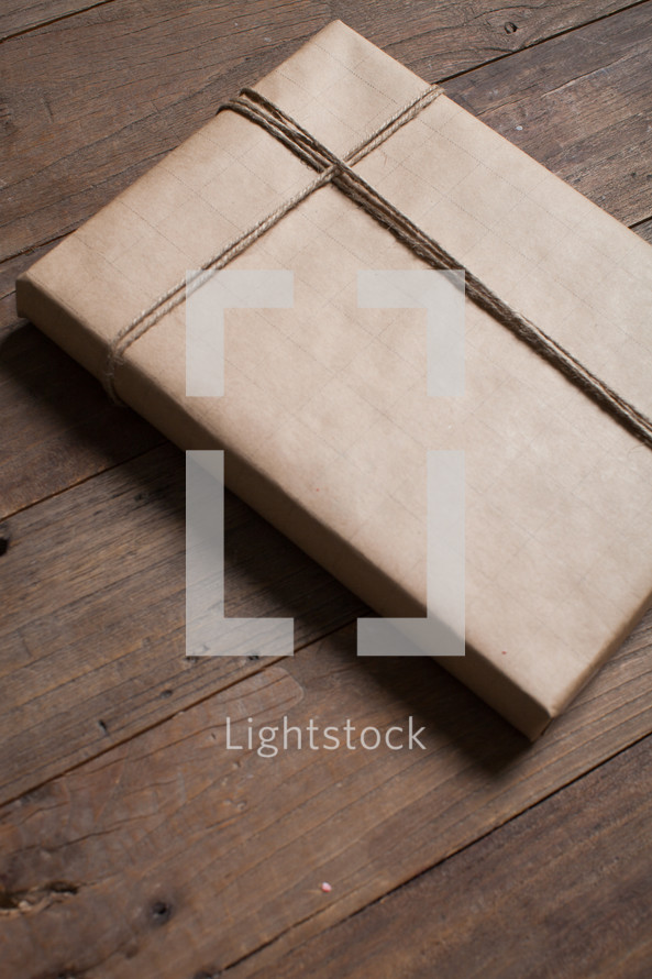 wrapped gift in brown paper on a wood floor