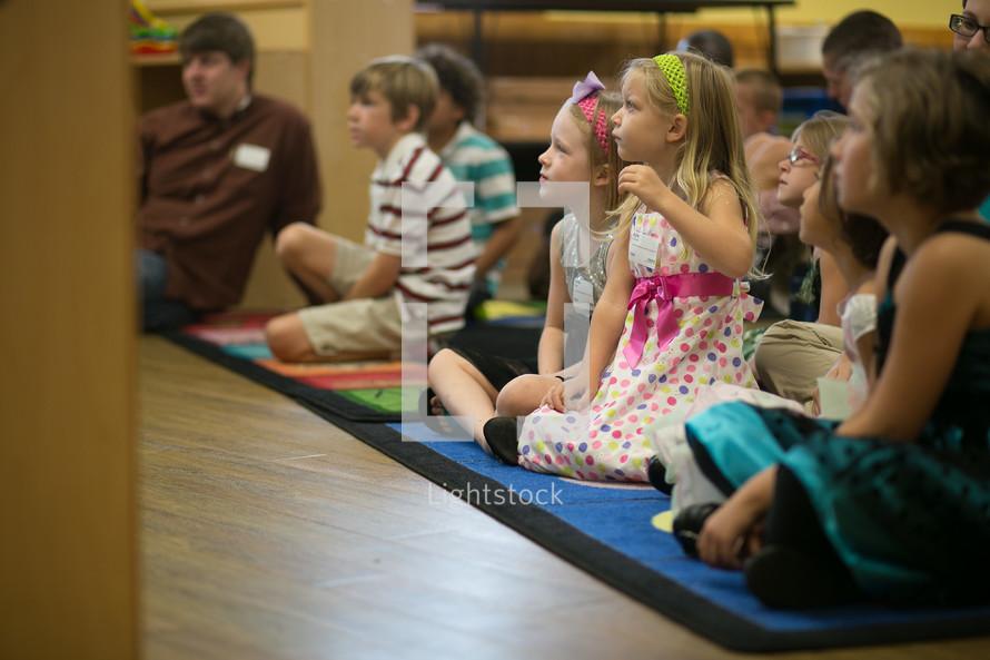 School children sitting on mat