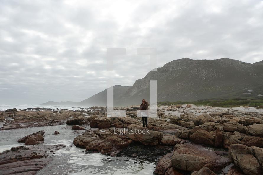 Woman standing on rocks on a coastal shore