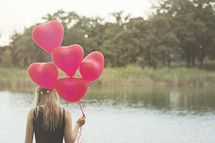 girl holding red Helium balloons by a lake