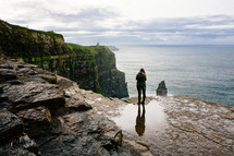 a woman standing at the edge of a sea cliff looking out over the ocean