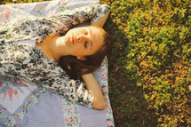 a woman sleeping on a blanket in the grass