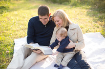 A family reading the bible outside