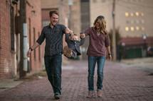 Man and woman walking along brick sidewalk at dusk swinging toddler boy in suit between them.