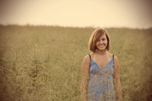 Teenager smiling and standing in a field