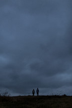 Couple standing on a hill with cloudy sky