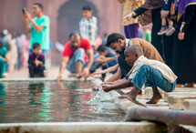 people washing their hands in a courtyard of a mosque in Delhi, India