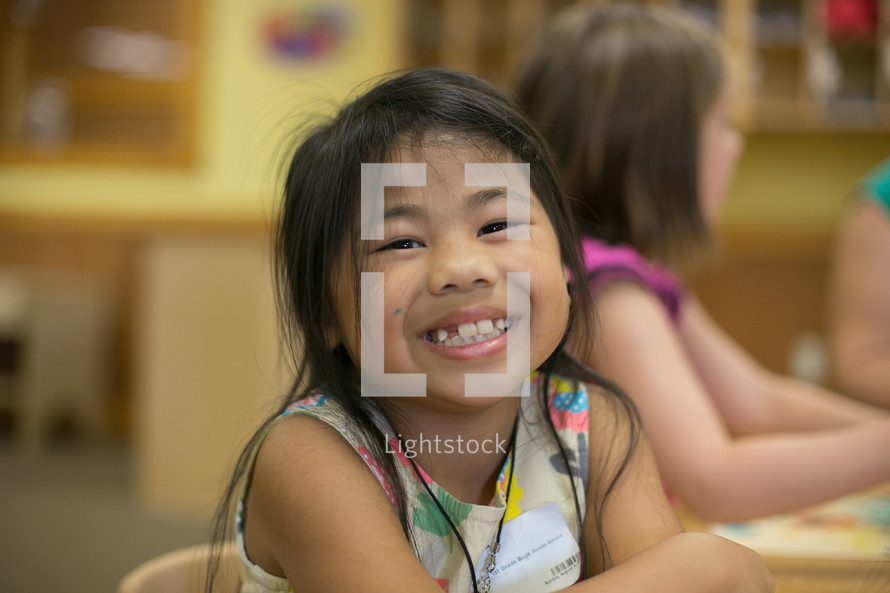 A young girl smiling in a classroom