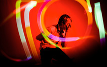 man with swirling lights at a performance with his hand over his face