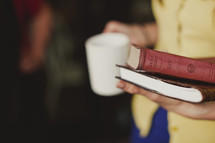 hand carrying a Bible and a journal