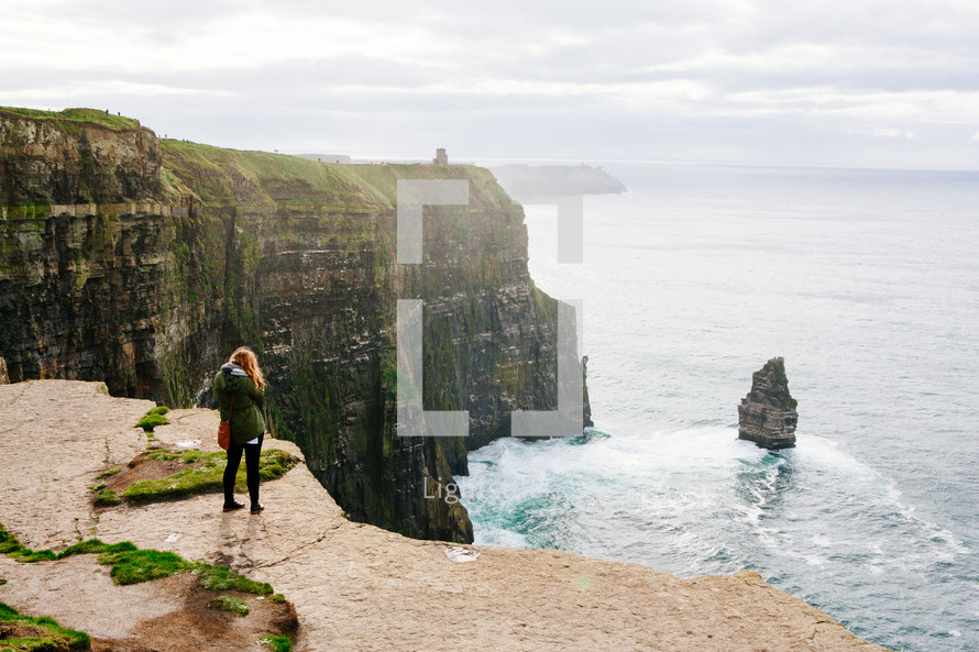 a woman standing at the edge of the Cliffs of Moher