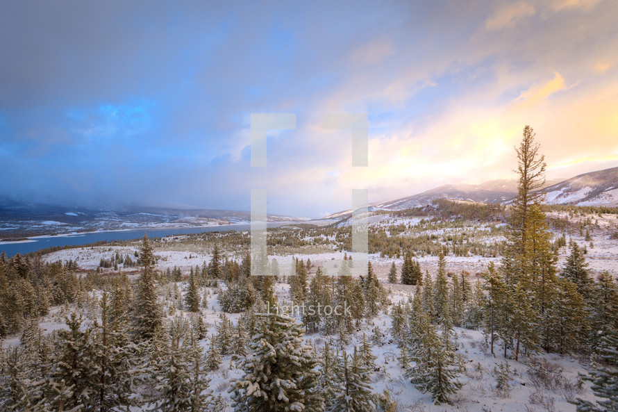 Rocky Mountains Colorado landscape with melting snow and evergreen trees near water at sunset