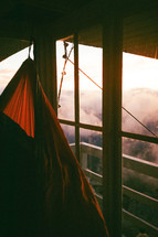 hammock on a deck overlooking mountain fog at sunrise