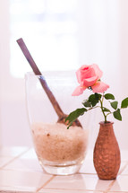 pink rose in a vase and bath salt in a cup