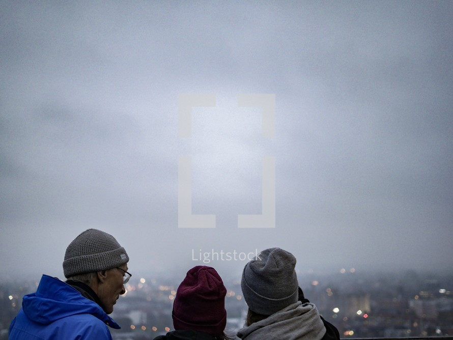 people looking out at a view over a foggy city in Poland