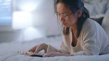 a young woman reading a Bible lying on her bed