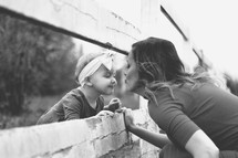 a mother kissing her toddler daughter through a fence