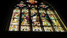 A huge stained glass window lights up a church with a biblical scene from scripture to be a light in the darkness and drawing church goers to worship and praise.
