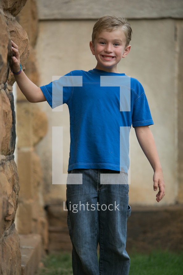 A young boy smiling next to a rock wall