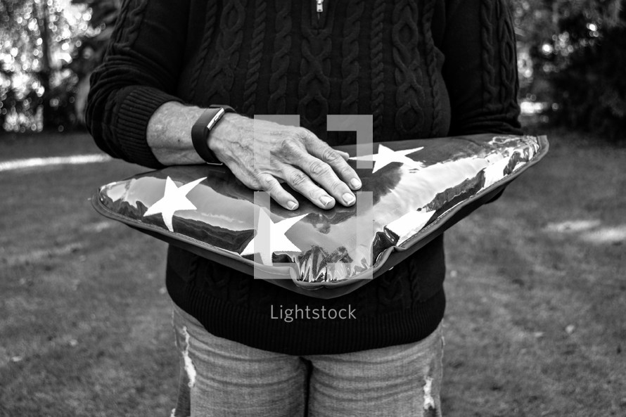 a woman holding a folded American flag