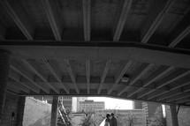 Bride and groom kissing under bridge