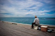 man sitting on a bench on a pier