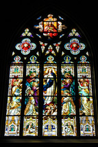 A huge stained glass window with multiple panels tells the story of Jesus Christ in an old historic church that is almost 200 years old in the southeastern United States.