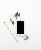 pencil, iPhone, and eucalyptus on a white background