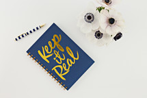 keep it real notebook and white flowers on a desk