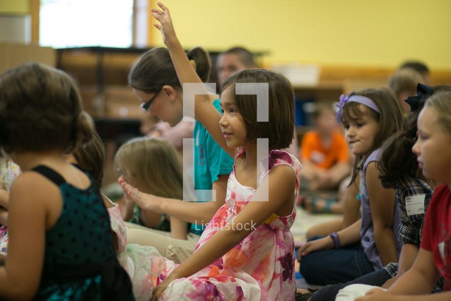 A little girl raising her hand