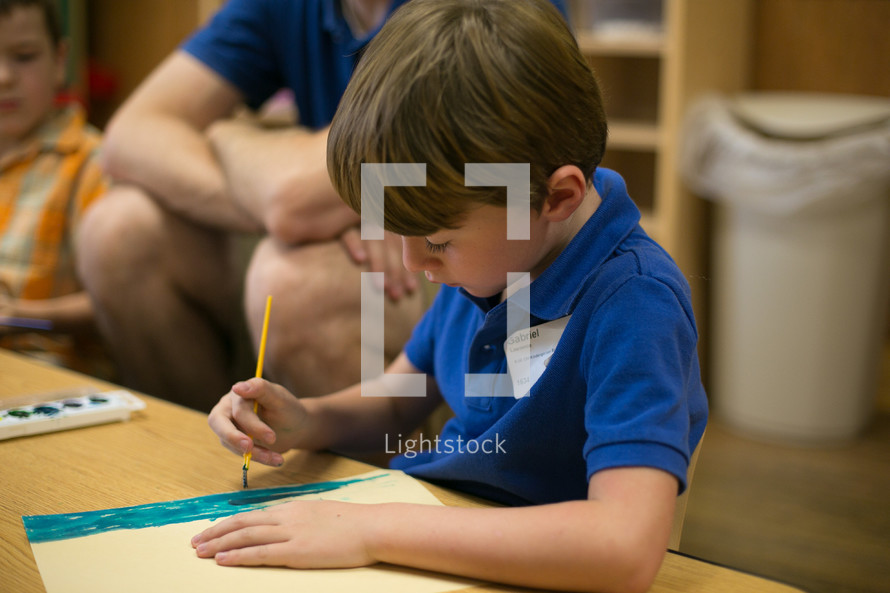 A boy using watercolors during children's church