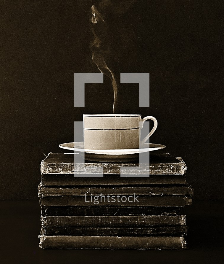 cup of steaming coffee on a stack of old books