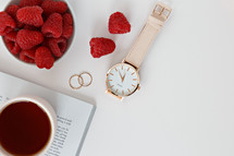 Raspberries in a bowl, watch, magazine, rings, and coffee cup
