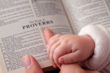 infants hand over mother's fingers and an open Bible