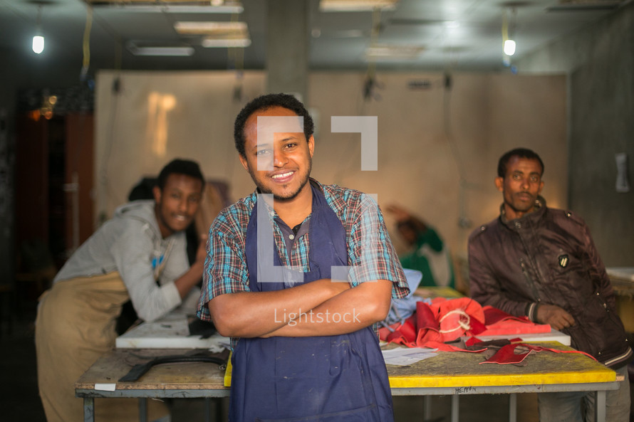 men in aprons in a factory making clothing