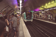 people gathered in an underground subway station in Paris