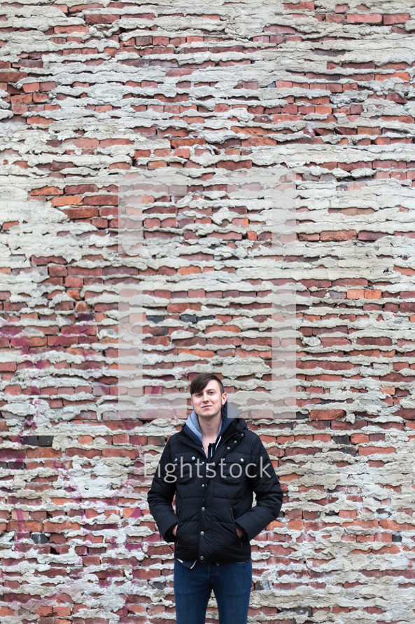 Man in a winter jacket standing in front of a brick wall.
