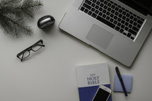 NIV Holy Bible, laptop, reading glasses, iPhone, post-it notes, pen, and pine boughs on a desk