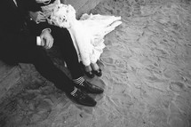 Bride and groom sitting on stone steps with shoes in the sand.