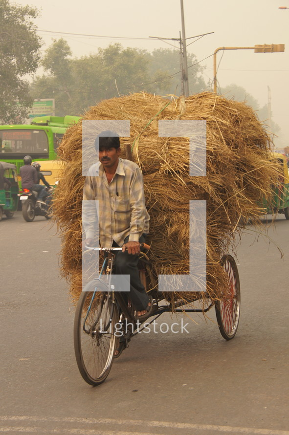 Man riding bicycle with hay on back